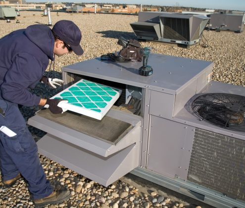 Worker changing a roof top air exhange units filter.
